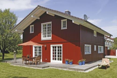 Feuerrote Holzfassade, blütenweiße Sprossenfenster, breiter Dachüberstand: Das Wohnhaus der Familie K. zeigt die Vorliebe der Bauherren für Skandinavien.