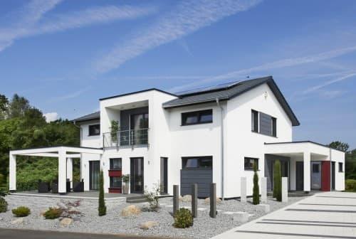 Einfamilienhaus mit Satteldach, Flachdach-Anbau und zweigeschossigen Erker.